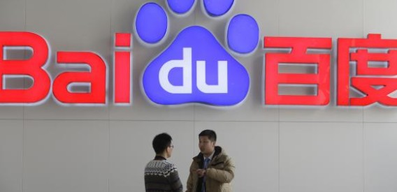 People talk in front of a Baidu's company logo at Baidu's headquarters in Beijing