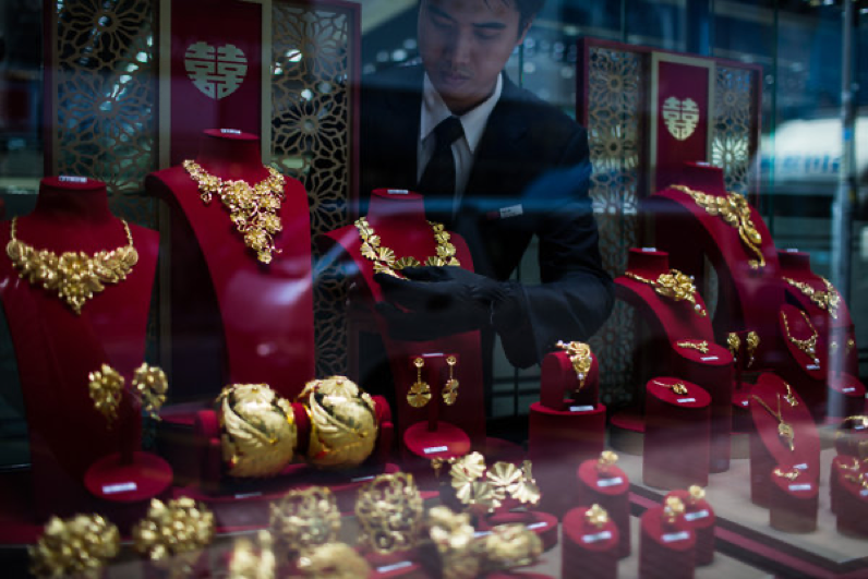 staff member at Chow Tai Fook arranges 24-karat gold items in th